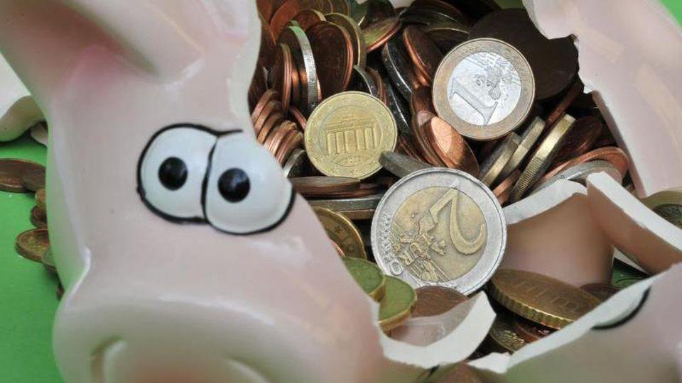 Ein Sparschwein mit Euro-Geldstücken liegt zerbrochen auf einem Tisch. Foto:Peter Kneffel/Archivbild