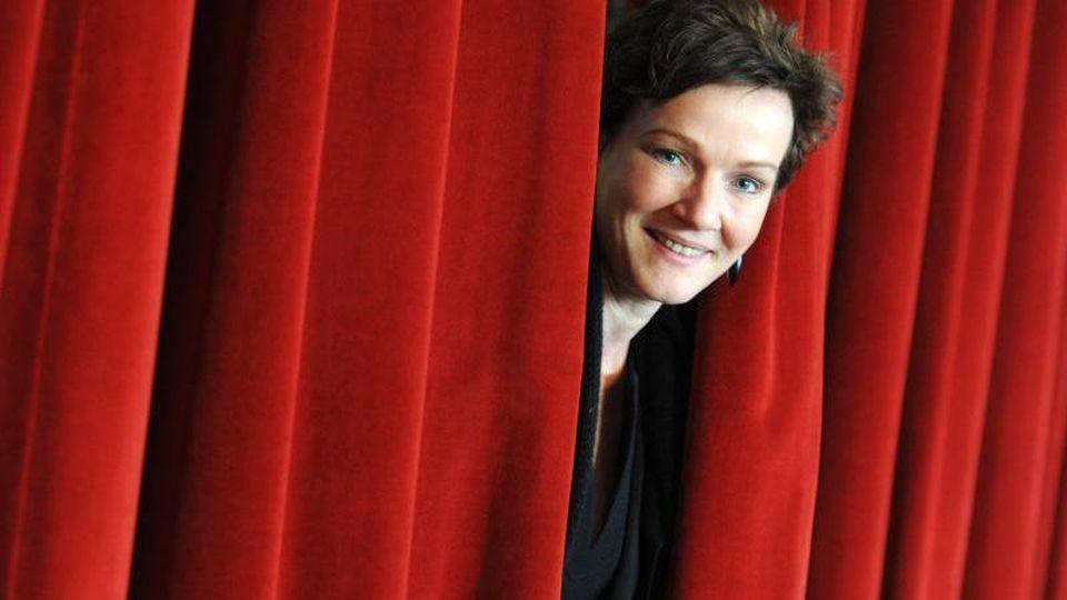 Karin Beier schaut zwischen einem Theatervorhang hervor. Foto: Marcus Brandt/dpa/Archivbild