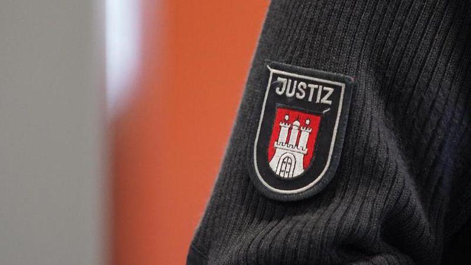 Ein Justizbeamter steht vor dem Sitzungssaal eines Gerichts. Foto: Marcus Brandt/dpa/Symbolbild