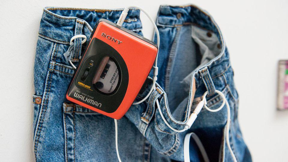 Ein Walkman von Sony hängt in einer Ausstellung an einer Jeans.
