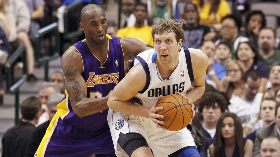 Lakers guard Bryant defends Mavericks forward Nowitzki in the low post during their NBA basketball game in Dallas, Texas