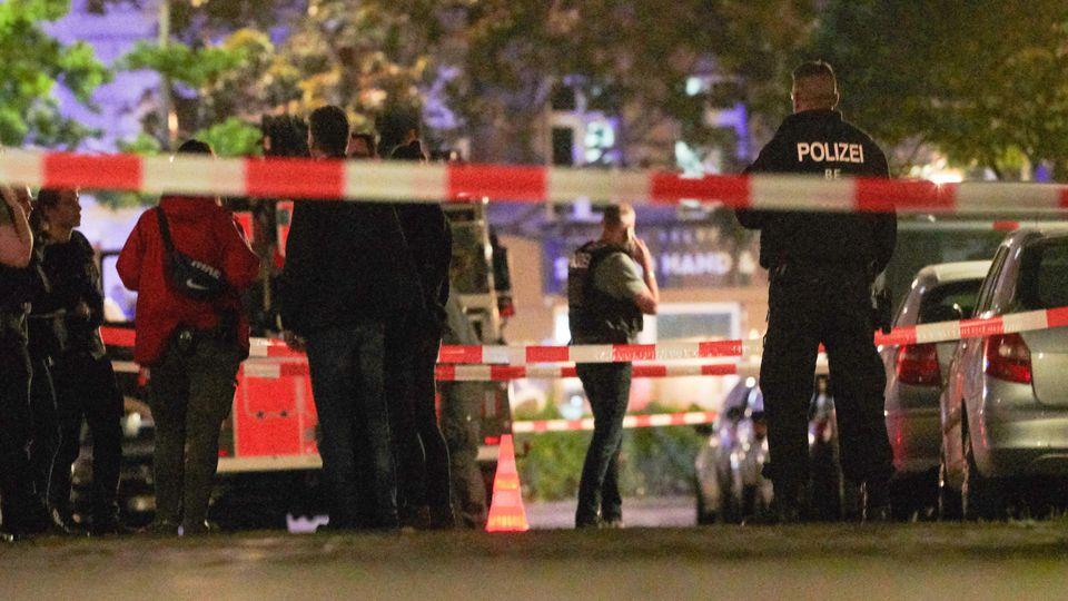 19.05.2019, Berlin: Polizeibeamte stehen hinter einer Absperrung an der Schinkestraße. Nach Angaben der Polizei wurde dort am Abend eine Person durch einen Schuss verletzt. Der Bereich wurde weiträumig abgesperrt. Die Kriminaltechnik der Polizei sich