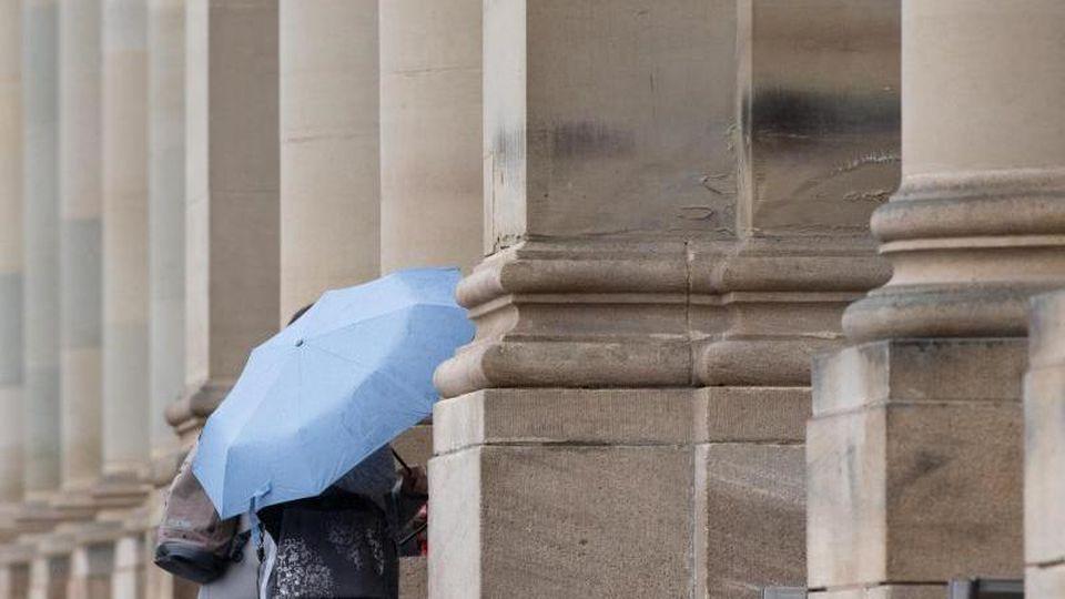 Eine Passantin hält auf dem Schlossplatz in einen Regenschirm in der Hand. Foto: Tom Weller/dpa/Archiv