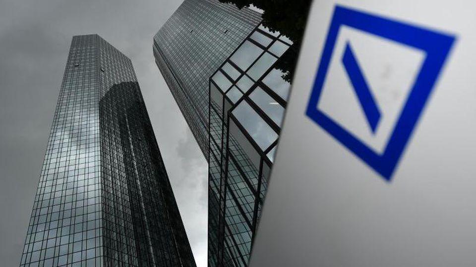 Dunkle Wolken, Deutsche Bank-Gebäude sowie das Logo der Bank. Foto: Arne Dedert/Archivbild