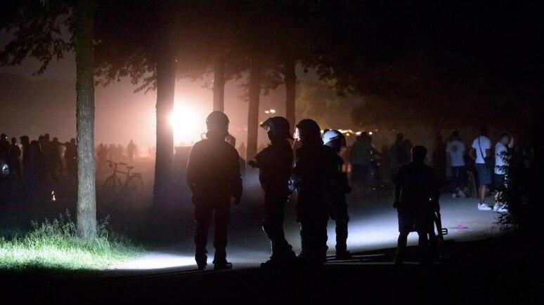 Behelmte Polizisten stehen am Rande der Stadtpark-Wiese und werden von einem Lichtmast angestrahlt. Die Polizei hat eine Party mit rund 3000 Menschen im Hamburger Stadtpark aufgelöst. Foto: Jonas Walzberg/dpa