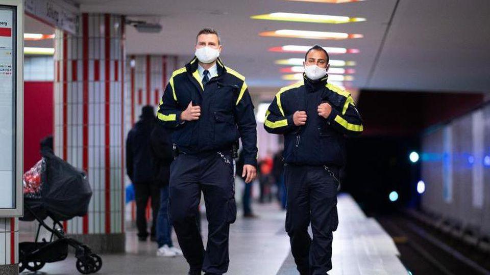 Mitarbeiter der Hamburger Hochbahn-Wache kontrolliert die Einhaltung der Maskenpflicht an einer U-Bahn-Haltestelle. Foto: Daniel Reinhardt/dpa/Archivbild