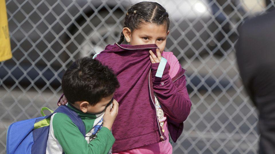 Kinder verlassen eine Schule und bedecken Nase und Mund