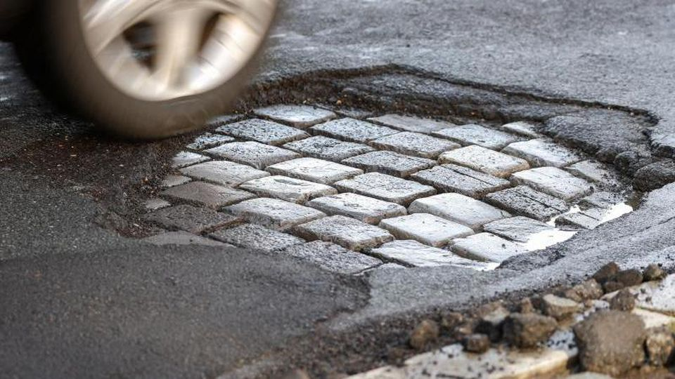 Ein Auto fährt über eine Straße mit Schlaglöchern. Foto: Jan Woitas/dpa-Zentralbild/dpa/Symbolbild