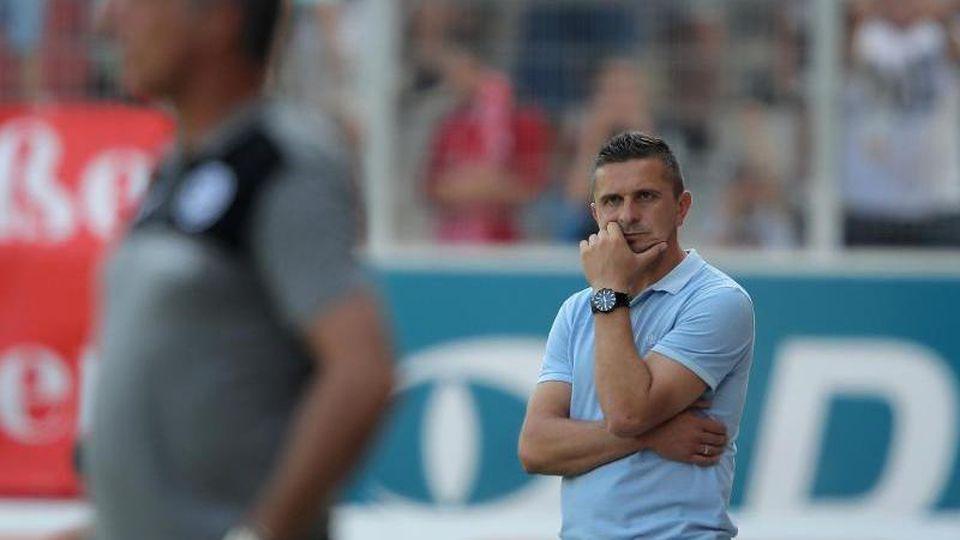 Der Regensburger Trainer Mersad Selimbegovic (r) verfolgt den Spielverlauf. Foto: Daniel Karmann