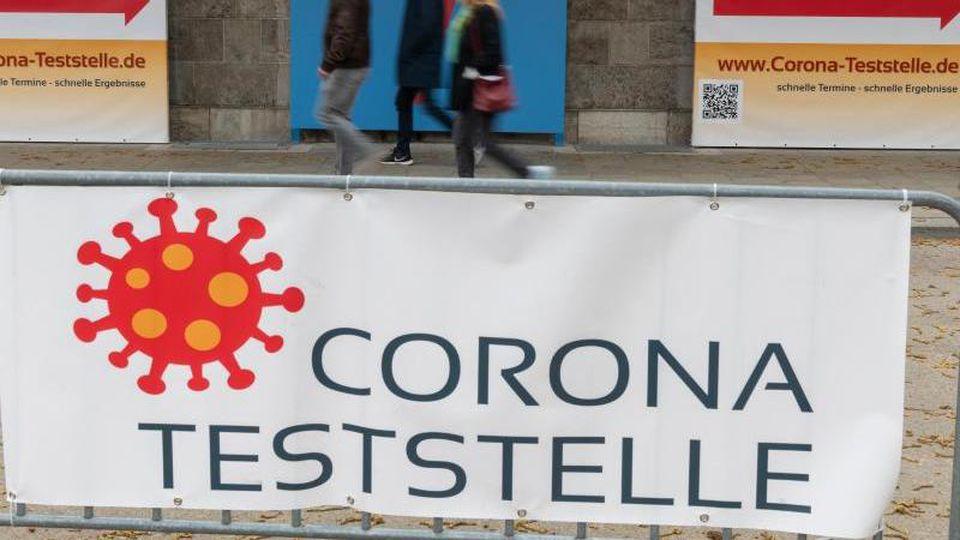 """Passanten gehen an Schildern mit der Aufschrift """"Corona Teststelle"""" vorbei. Foto: Peter Kneffel/dpa"""