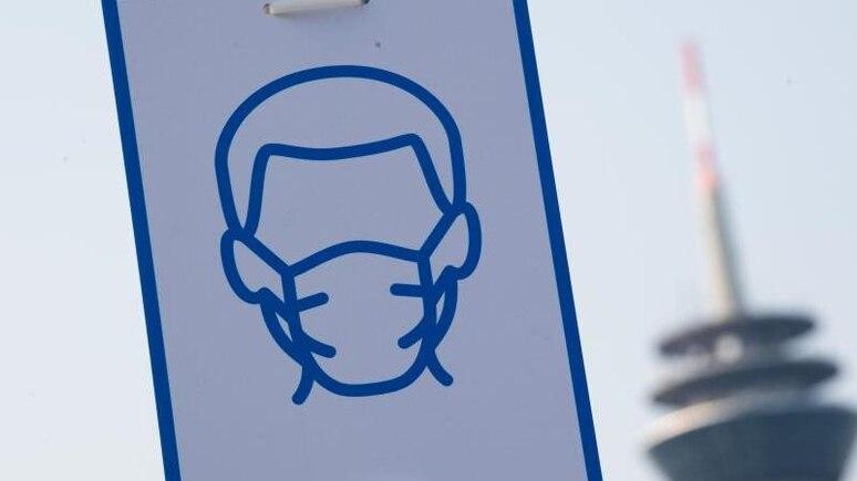 Ein Piktogramm weist in Düsseldorf auf das Einhalten der Maskenpflicht hin. Foto: Federico Gambarini/dpa