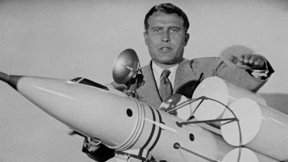 ARCHIV - 12.06.2019, ---: Das undatierte Foto mit einem unbekannten Aufnahmeort zeigt den US-amerikanischen Raketenkonstrukteur deutscher Herkunft Wernher von Braun an einem Modell einer Rakete. (zu dpa «Von den Nazis zur Nasa: Der deutsche Anteil an