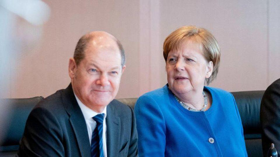 Bundesfinanzminister Olaf Scholz und Bundeskanzlerin Angela Merkel während einer Kabinettsitzung. Foto: Kay Nietfeld/dpa