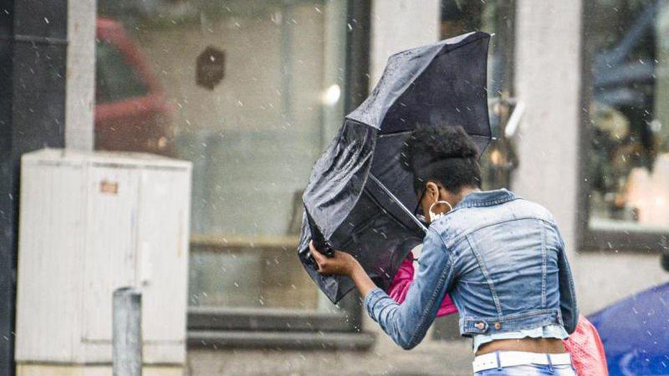 Eine Frau überquert bei starkem Wind und einsetzendem Regen eine Straße. F. Foto: Frank Rumpenhorst/dpa