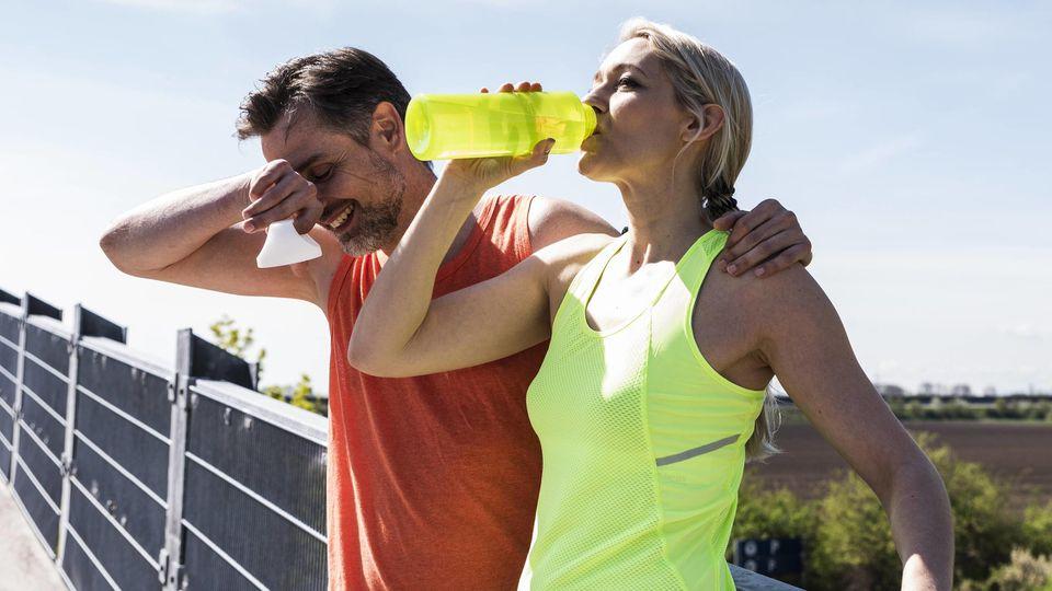 Fit couple jogging in the city having fun taking a break model released Symbolfoto PUBLICATIONxINx