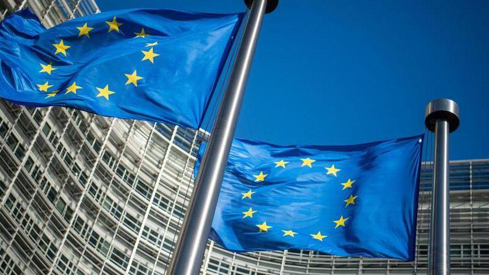 Flaggen der Europäischen Union wehen im Wind vor dem Berlaymont-Gebäude, dem Sitz der Europäischen Kommission inBrüssel. Foto: Arne Immanuel Bänsch/dpa
