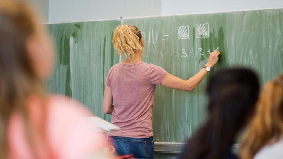 Eine junge Lehrerin schreibt an eine Schultafel. Foto: Julian Stratenschulte/Archivbild