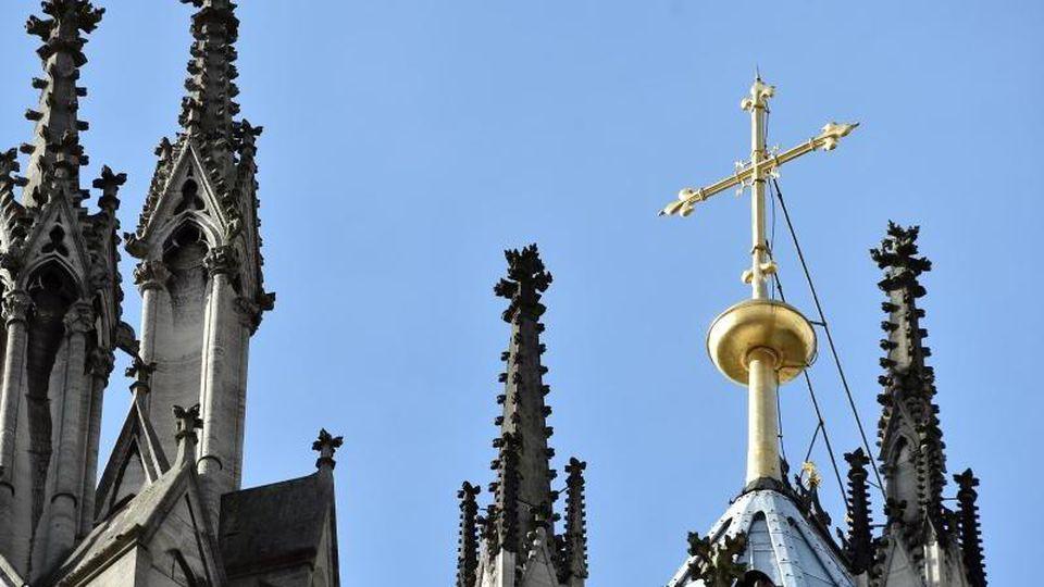 Ein goldenes Kreuz auf dem Kölner Dom leuchtet in der Sonne. Foto: Caroline Seidel/Archiv
