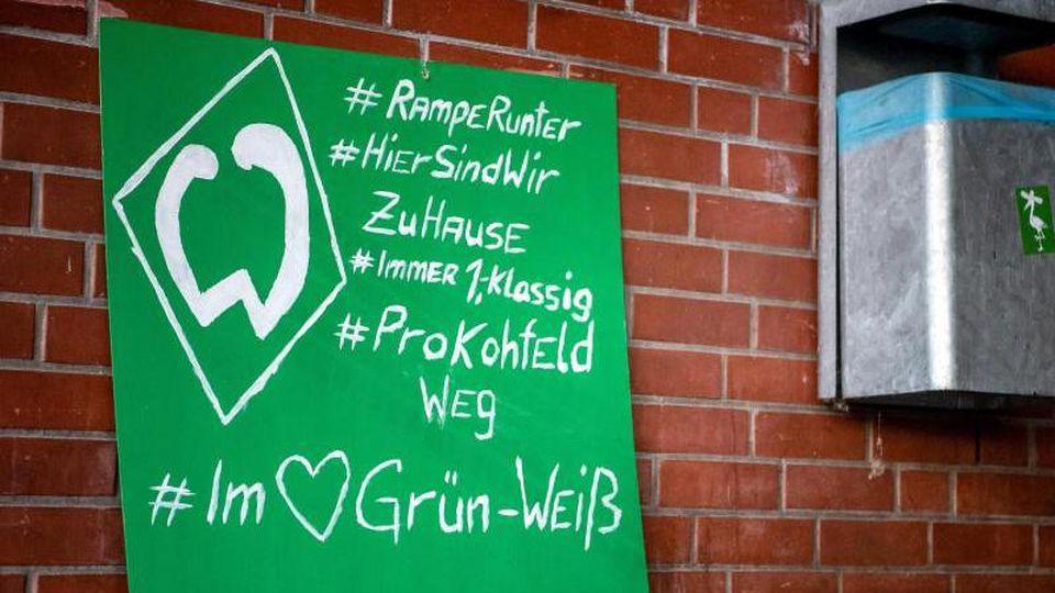 Ein Plakat von Werder-Bremen-Fans am Weserstadion. Foto: Sina Schuldt/dpa