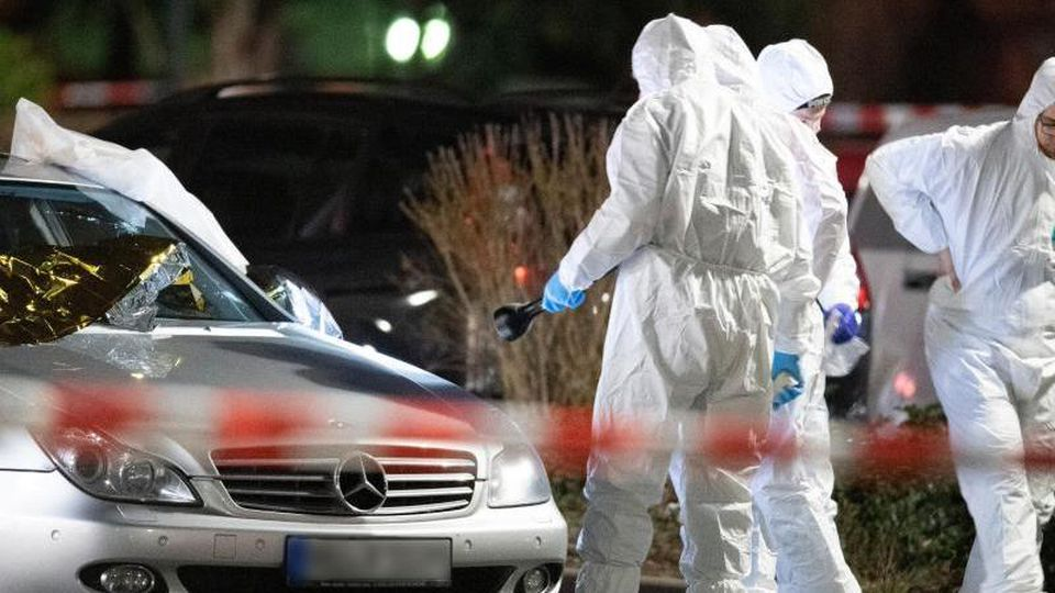Forensiker arbeiten an einem Tatort in Hanau-Kesselstadt an einem Mercedes. Foto: Boris Roessler/dpa