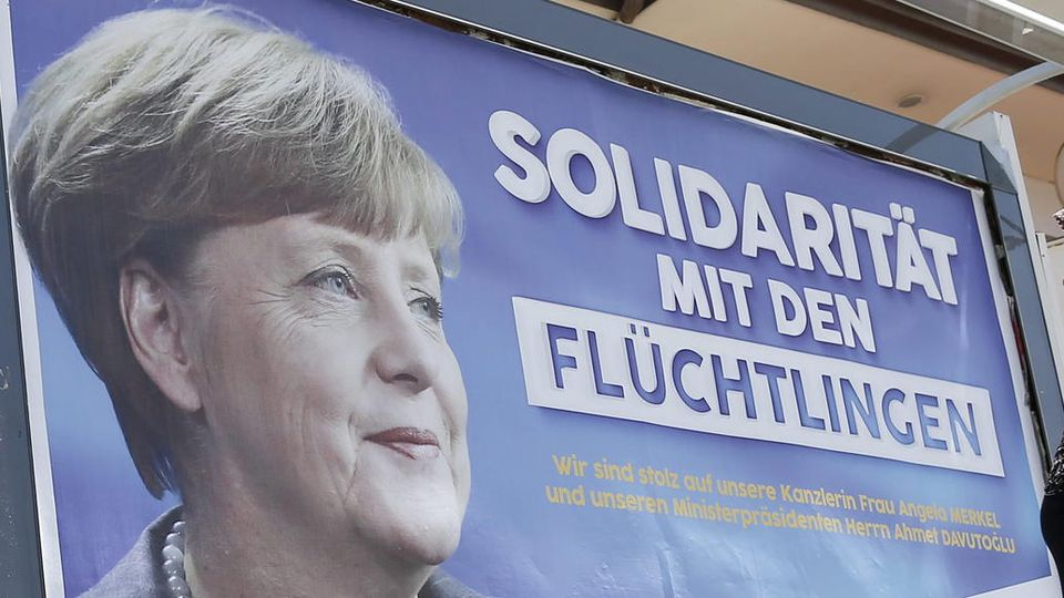 """FILE- People walk in front of billboards with the picture of German Chancellor Angela Merkel with the words; 'Solidarity with the refugees', in Gaziantep, Turkey, 23 April 2016.  EPA/SEDAT SUNA (zu dpa-KORR.: """"Wie Merkel in einer Nacht das Land gepr"""
