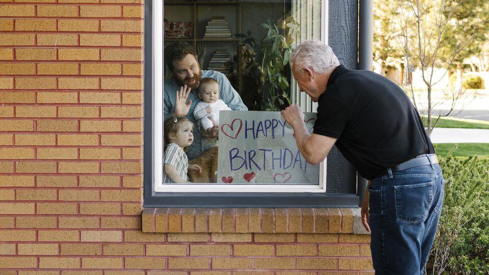 Großvater besucht während der Corona-Pandemie seine Familie am Fenster.