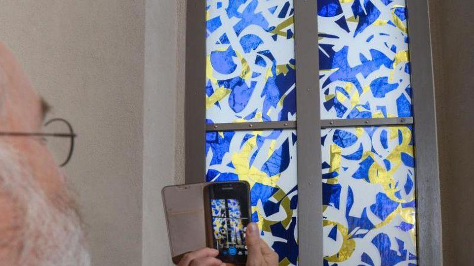 Eines der drei neuen Chorfenster in der Dorfkirche von Großbadegast. Foto: Heiko Rebsch/zb/dpa