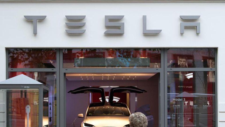 Ein Tesla-Modell steht mit aufgeklappten Türen im Showroom am Kudamm. Foto: Soeren Stache/zb/dpa