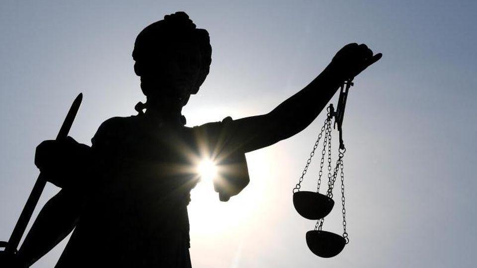 Eine Statue der Justitia hält eine Waage in ihrer Hand. Foto: Arne Dedert/dpa/Archivbild