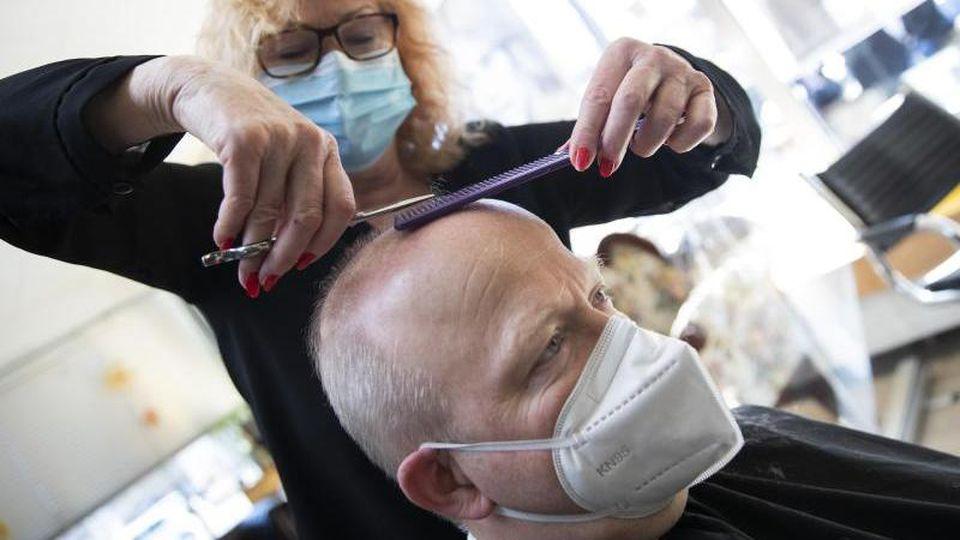Eine Friseurmeisterin schneidet die Haare von Michael Theurer. Foto: Tom Weller/dpa