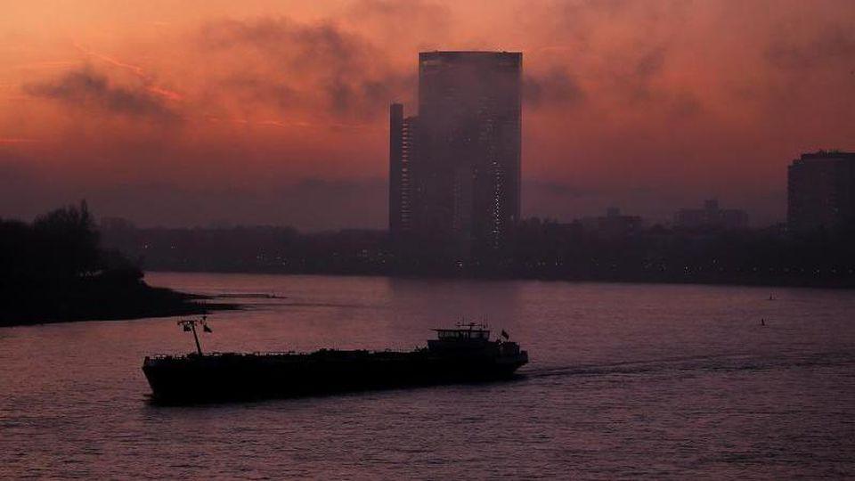 Ein Schiff fährt im Morgennebel über den Rhein. Foto: Oliver Berg/dpa/Archivbild