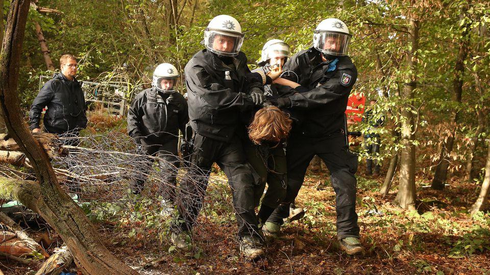 24.09.2018, Nordrhein-Westfalen, Manheim: Im Hambacher Forst wird ein Aktivist von Polizisten abgeführt. Die Behörden setzen die Räumung von Baumhäusern der Aktivisten fort. Nach Angaben des NRW-Innenministeriums wurden am Montag die ersten Räumungsv