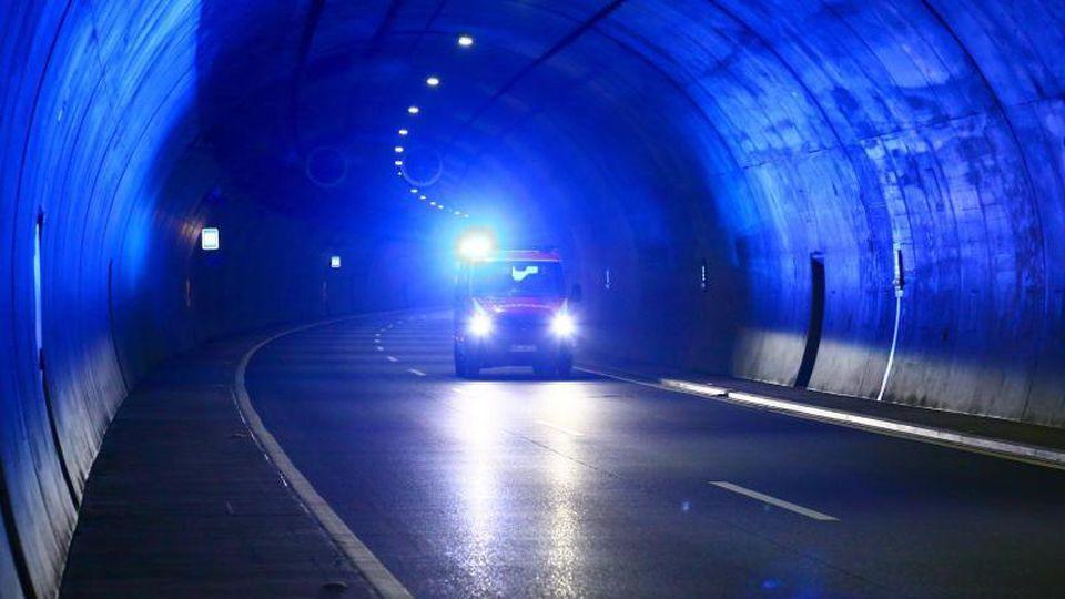 Ein Rettungsfahrzeug fährt mit eingeschaltetem Blaulicht durch einen Tunnel. Foto: Bodo Schackow/zb/dpa/Archivbild