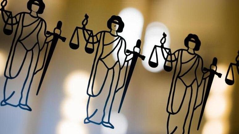 Die Justitia ist an einer Scheibe am Eingang zum Oberlandesgericht zu sehen. Foto: Rolf Vennenbernd/dpa/Symbolbild
