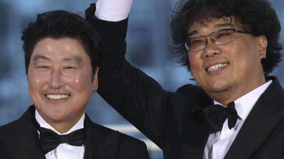 """Schauspieler Kang-Ho Song (l) und Regisseur Bong Joon-ho feiern die """"Goldene Palme"""" für den Film """"Parasite"""". Foto: Petros Giannakouris/AP"""