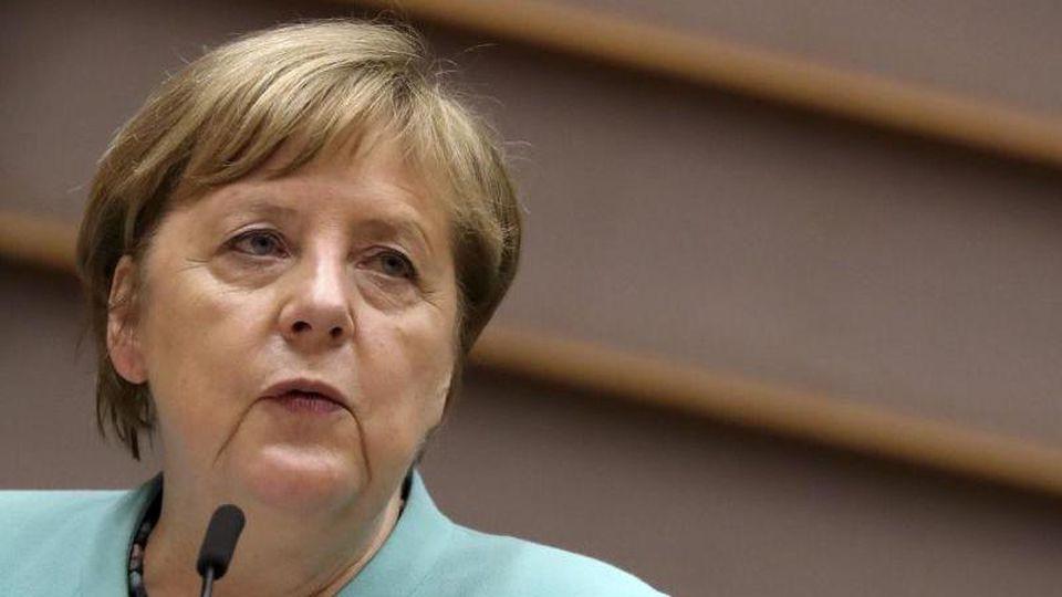 Bundeskanzlerin Angela Merkel (CDU) spricht in ein Mikrofon. Foto: Yves Herman/Reuters Pool/AP/dpa/Archivbild