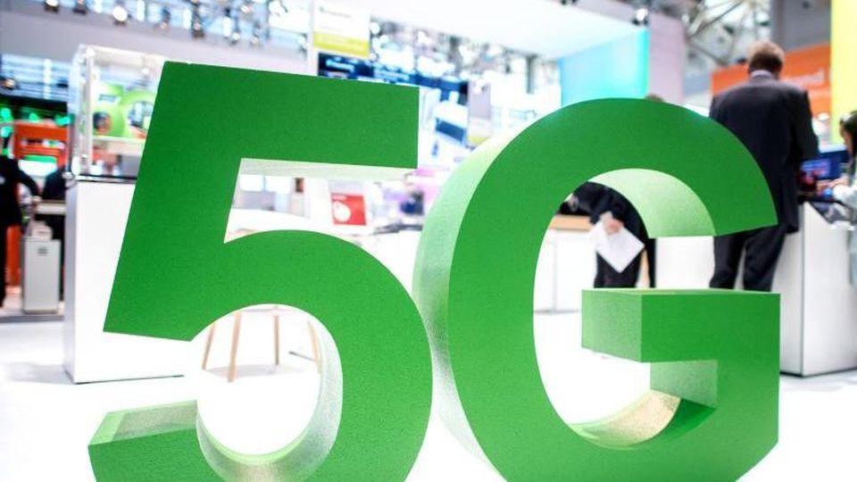 Ein Symbol für den Netzstandard 5G steht auf einer Messe. Foto: Hauke-Christian Dittrich/Archivbild