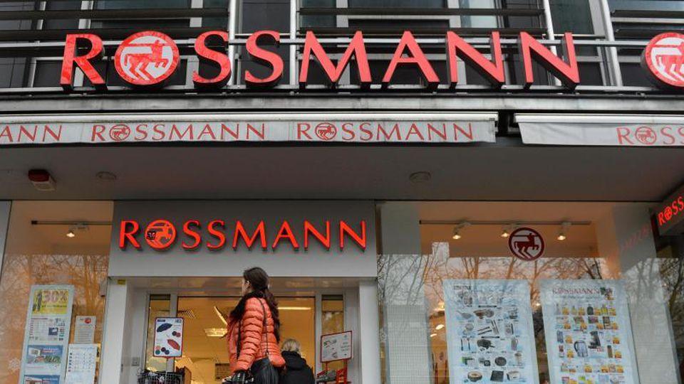 Eine Frau geht an einer Rossmann-Filiale vorbei.