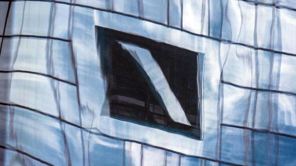 Die Zentrale der Deutschen Bank spiegelt sich in einer Glasfassade. Foto: Boris Roessler/dpa/Symbolbild