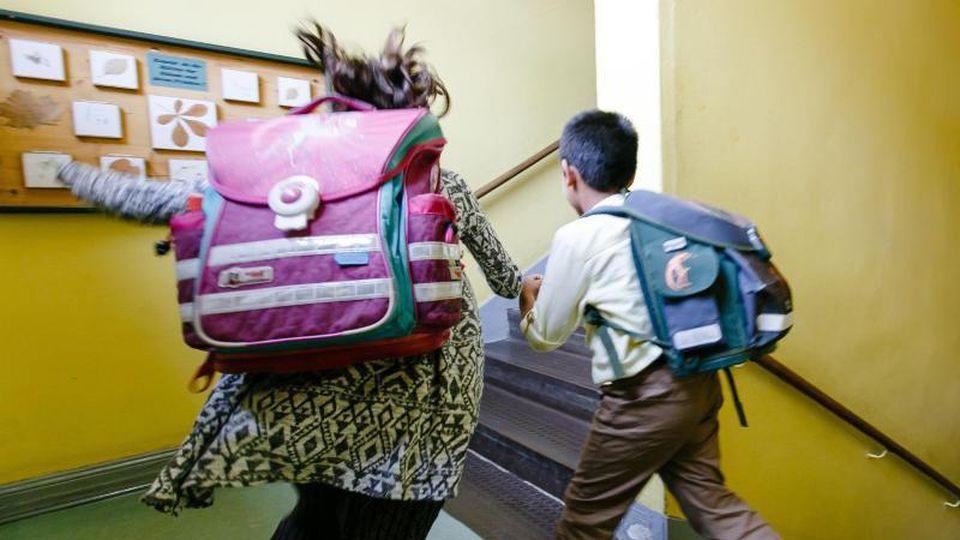 Zwei Schulkinder laufen durch das Treppenhaus ihrer Grundschule. Foto: Frank Molter/dpa/Archivbild