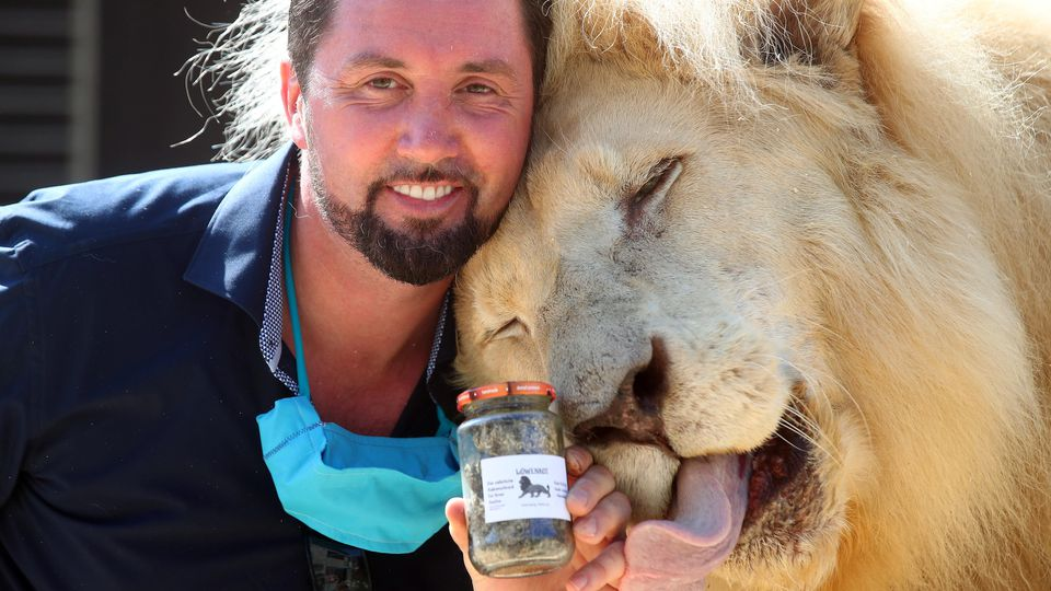 Lion tamer Lacey poses with Lion King Tonga and a glass of lion droppings in Munich