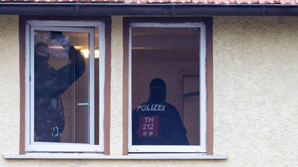 Polizisten durchsuchen ein Haus, das der rechten Szene zuzuordnen ist. Foto: Michael Reichel/dpa-Zentralbild/dpa