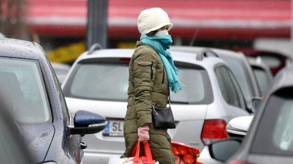 Eine Frau mit Mundschutz trägt ihre Einkäufe über den Parkplatz eines Einkaufszentrums in Salzburg. Foto: Barbara Gindl/APA/dpa