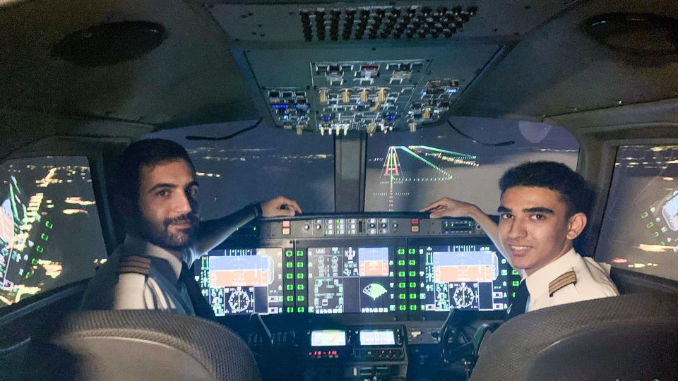Seth Van Beek (right) who has become the UK's youngest qualified commercial pilot aged just 18. He is pictured here with colleague Paris Antoino in a flight simulator at the Egnatia Aviation Training college. See SWNS sto