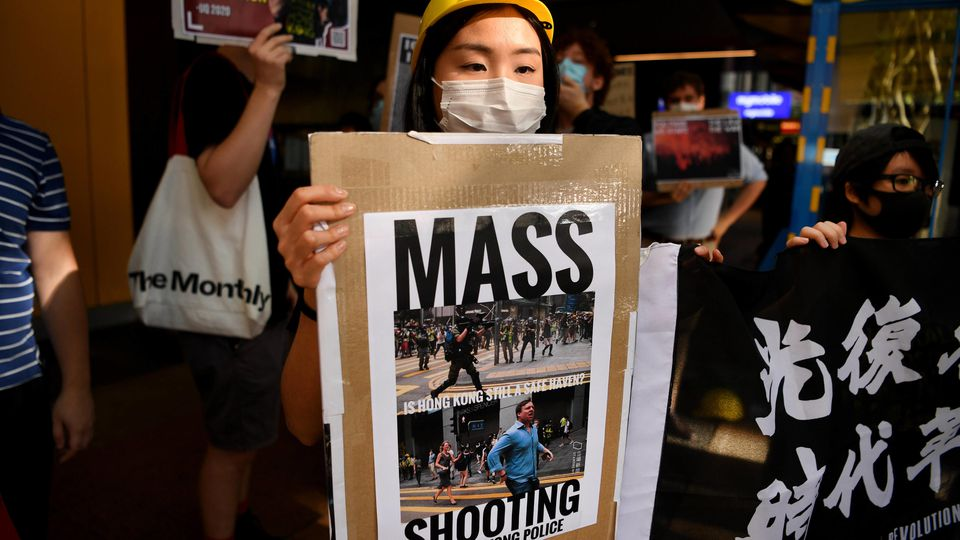 HONG KONG PROTEST DREW PAVLOU, A protester holds a sign during a demonstration in support of Hong-Kong, outside the Chi