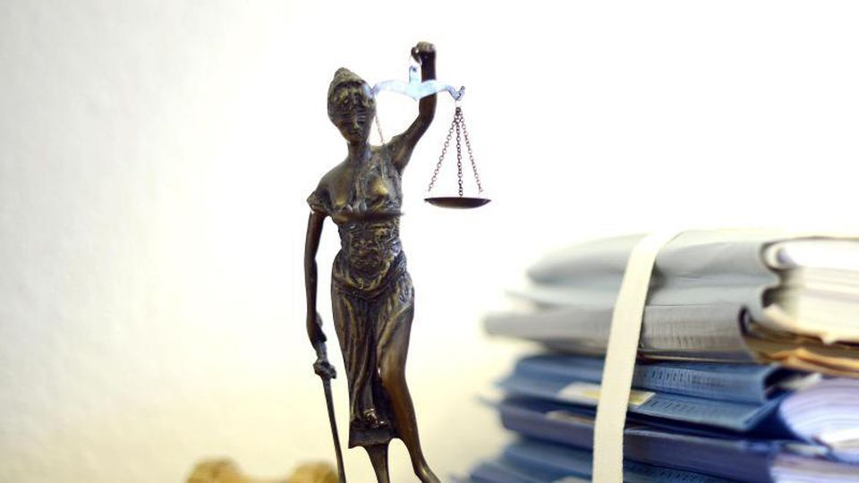 Eine Statue der Justitia steht neben Aktenbergen. Foto: Volker Hartmann/dpa/Symbolbild