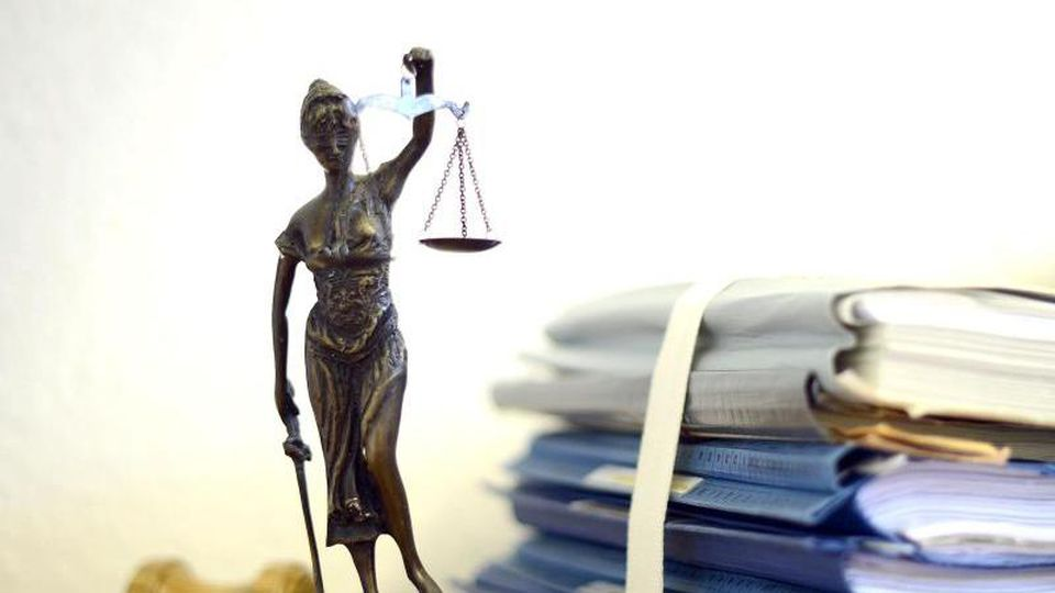 Eine modellhafte Nachbildung der Justitia neben Aktenordnern. Foto: Volker Hartmann/dpa/Archivbild