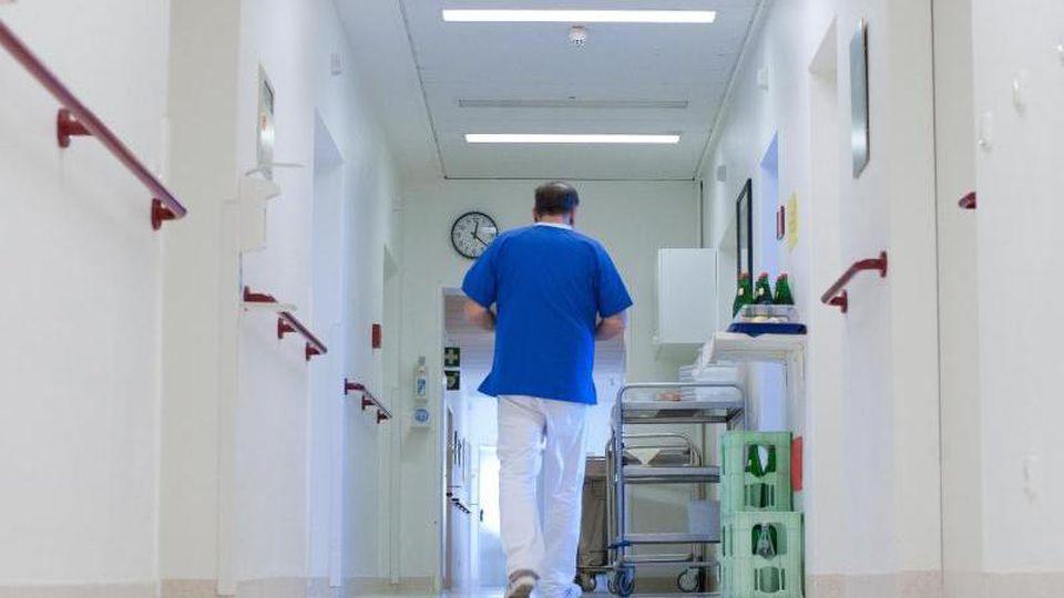 Ein Krankenpfleger geht über einen Flur in einem Krankenhaus. Foto: Philipp Schulze/dpa/Archiv/Illustration