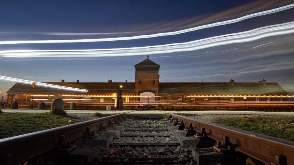 Lichter sind vor dem Eingangsportal des ehemaligen Konzentrationslagers Auschwitz-Birkenau zu sehen. Foto: Robert Michael/dpa-Zentralbild/dpa