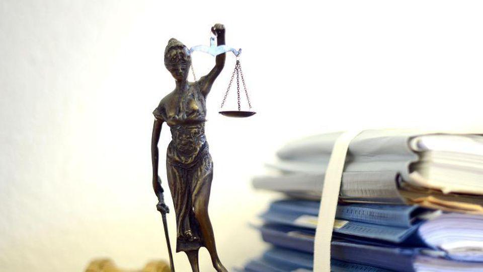 Justitia mit Holzhammer und Aktenstapel. Foto: Volker Hartmann/dpa